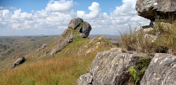 grand rocher étrangement posé en haut d'une crête avec une croix à son sommet